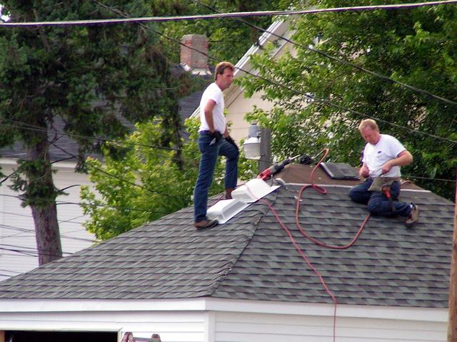 chlápci pracující na střeše domu